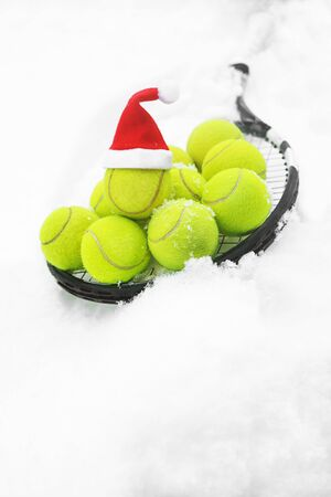 Tennis winter concept with tennis balls and racket on white snow, isolated. Top view, copy space. Merry Christmas and Happy New Year sport healthy layout. Santa Claus hat on the top off ball. Stock Photo