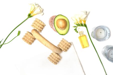 Beauty SPA sauna concept avocado, body massager, skin care facial essence oil, flower and towel on white background. Natural cosmetics. Healthy skin, facial and body care. Flat lay. Selective focus.