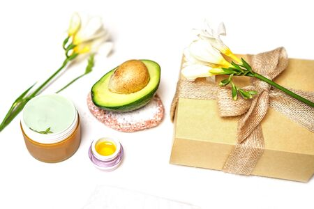 Beauty SPA sauna concept avocado, skin care facial essence oil, flower, gift box and towel on white background, isolated. Natural cosmetics. Healthy skin facial and body care. Selective focus. Фото со стока