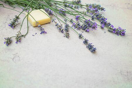 Lavender flowers and natural soap for bodycare on concrete background. Flat lay, top view. Spa massage concept. Copy space.