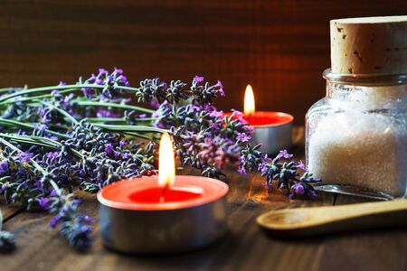 Spa massage setting with lavender flowers, scented aroma candles and cosmetic salt on wooden background. Close-up. Copy space.