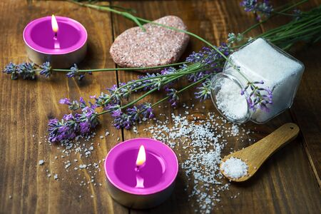 Spa massage setting with lavender flowers, scented aroma candles and flavored salt on wooden background. Close-up. Copy space. Фото со стока