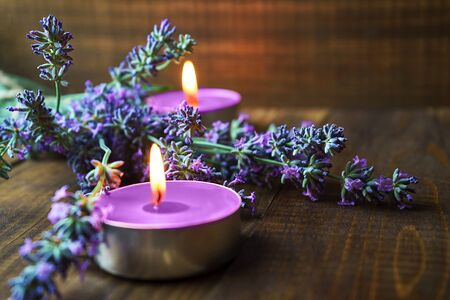 Spa massage setting with lavender flowers, scented aroma candles on wooden background. Close-up. Copy space.