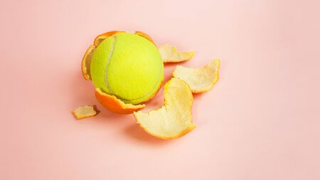 Tennis ball in an orange, concept on trendy pink coral