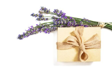 Beauty setting with lavender flowers and gift box natural color with bow on white background, isolated. Close-up. Copy space. Flat lay, top view. Beauty, medical clinic, spa concept.