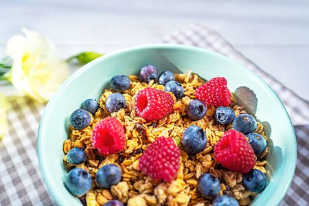 Bowl of homemade granola with fresh berries on gray wooden background. Top view, flat lay. Trendy mint green blue color of bowl and shadows on the table.