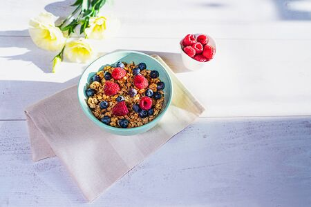 Bowl of homemade granola with fresh berries on gray wooden background. Top view, flat lay. Trendy mint green blue color of bowl.