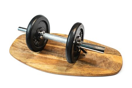 Black heavy dumbbell on cutting board and white background, isolated. Sport concept for weight loss. Close up, place for text.