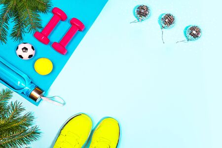 Christmas sport set with pink dumbbells, bottle of water, fir tree branches, soccer, tennis ball on yoga mat and disco balls, yellow sneakers on blue background. Flat lay, top view, copy space.