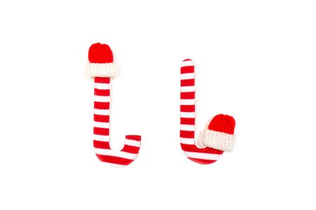 Close up shot of a Christmas Decoration item. Happe New Year concept with red and white Christmas stick or cane wearing on red cap on white background, isolated. Flat lay, top view. Stockfoto