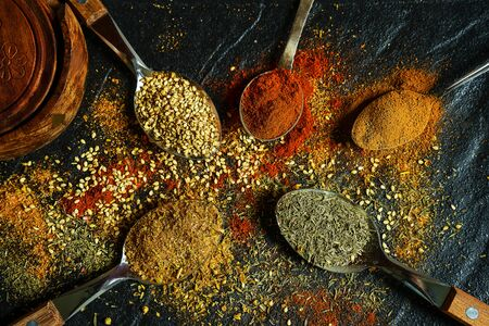 Different kind of spices on a black stone. Oriental spices in spoons, peppers, curry powder, herbs on black metallic tray in Asian style. Flat lay, top view. Фото со стока