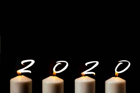 Marry Christmas and happy New Year. 2020 is written with candle flames on black background. Concept of greeting card. Top view, flat lay, copy space. Stock Photo