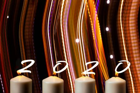 Happy New Year 2020 is written with candle flames on party striped colors Stock Photo