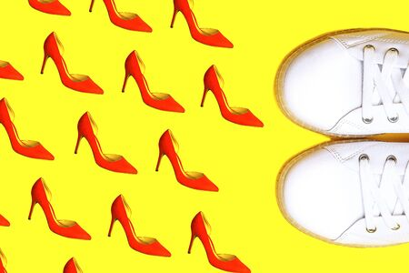 Fashion white sneakers against female red shoes pattern on bright yellow background. Party, Valentines Day, Christmas, Happy New Year, Black Friday, wedding outfit conception. Flat lay, top view. 写真素材