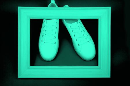 Fashion sneakers and wooden frame on neo mint color Banco de Imagens