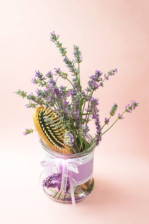 Wooden scalp and massage brush and hair comb with lavender flowers on pastel pink