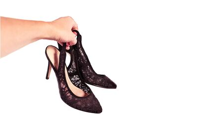Woman holds fashionable black lace shoes in her hand, isolated.