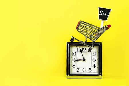 Christmas Black Friday Sale concept with silver clock, shopping cart shop trolley with sign sale on yellow Stock fotó