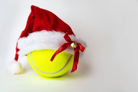 Christmas and New Year concept with Santa hat on tennis ball on gray background. Winter sport healthy layout. Holiday conception. Place for your text.