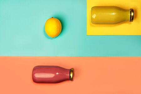 Bottles of multicolored juices or smoothies and lemon on yellow, pink coral and trendy mint green blue background. Flat lay, top view, close up. Minimal style. Zdjęcie Seryjne