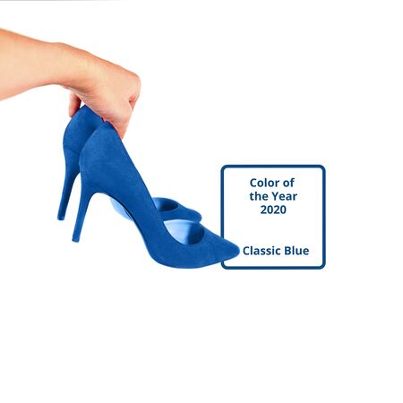 Woman holds fashionable blue shoes in her hand, isolated. Concept Black Friday Sale, Valentines day, Christmas, New Year party. Classic blue color of the year 2020. Stock Photo