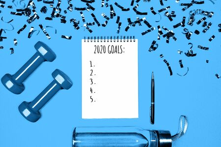 Goals list for New Year Holiday. Christmas sport set with dumbbells, notebook with pen, bottle of waterwater and colorful confetti on classic blue color background. Flat lay, top view, copy space. Stock Photo