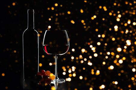 Elegant red wine glass, wine bottle and bunch of grapes on the dark background and blurred defocused lights as Christmas decorations background. Party concept. Valentine's day, Birthday concept. Imagens