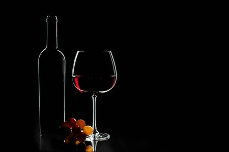 Elegant red wine glass, wine bottle and bunch of grapes on the dark background. Valentine's day, Birthday concept.