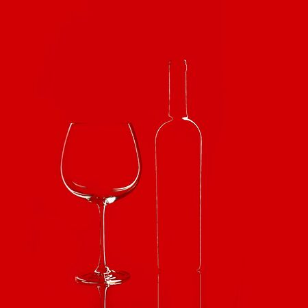 Empty wine glass and a bottle isolated on red background. Elegant red wine glass and a wine bottle. Valentine's day, Birthday concept.