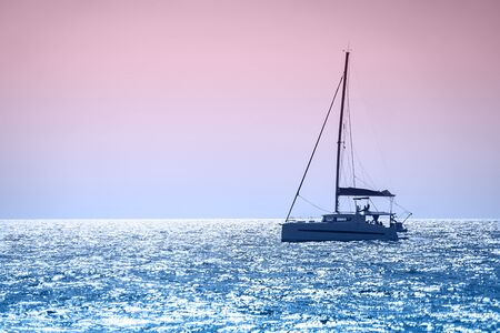 Sailboat boat in the open blue sea in Greece, on sunset time. Yachting. Turquoise waters of Aegean Sea. Famous travel sailing destination in Europe. Classic Blue color 2020 concept.