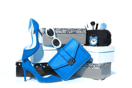 Party outfit composition trendy fashion female accessories blue shoes sunglasses handbag clutch on carton boxes on white background. Top view, flat lay. Classic Blue color 2020 concept.