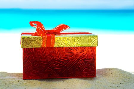 Red gift box on the sea sand. Gift concept for Valentine Day, wedding, Christmas or summer tropical vacation.