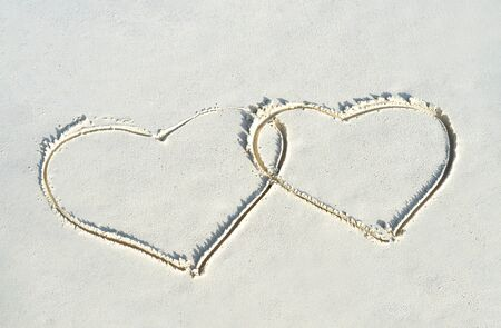 Heart shape on white yellow sand beach. Love concept for Valentine Day or summer vacation. Banco de Imagens