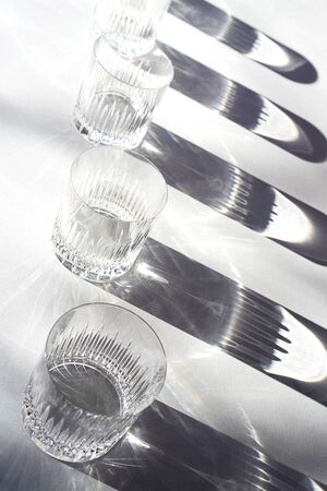Trendy pattern made with glasses and shadows on gray white background. Sunlight through glass of water. Stock fotó