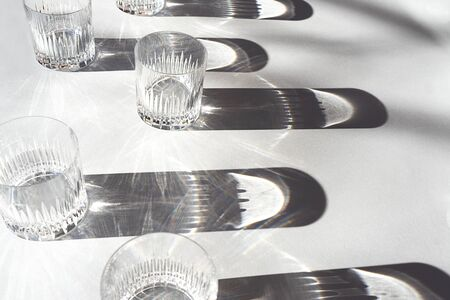 Trendy pattern made with glasses and shadows on gray white background. Sunlight through glass of water. Stockfoto