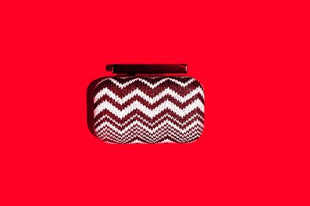 Valentines day, Christmas concept with stylish clutch bag clutch on classic red color backdrop. Trendy handbag with shadow. Copy space for text.
