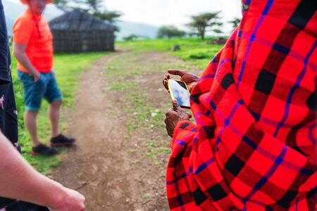 African man in traditional dress holding a cellphone. Tanzania, Africa. Close up.