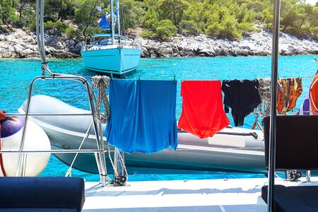 Sailing yacht catamaran and swimwear on the turquoise waters of sea background. Greece. Famous travel sailing destination in Europe. Sailboat. Selective focus.
