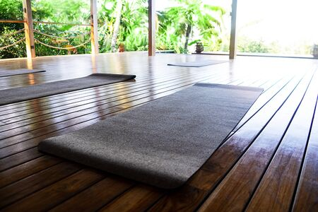 Open tropical yoga studio place with view outside to the beautiful garden with palm trees and ocean. Holiday concept. Standard-Bild