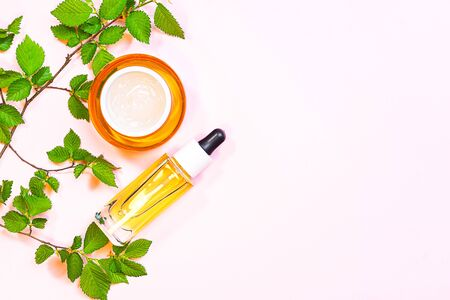 Skin care beauty products, natural cosmetic. Flat lay image on pink background. Natural cosmetic skincare bottle, serum and organic green leaf. Homemade and beauty product concept.
