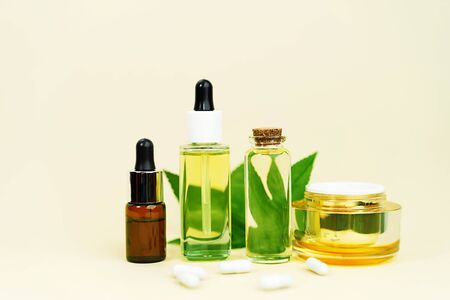 Glass bottles with herbal CBD oil, THC tincture, cream, pills and hemp leaf on pastel beige background. Flat lay, minimal style. Cosmetics CBD oil. Essential natural oils for face and body.
