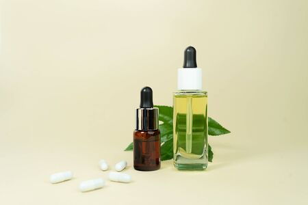 Various glass bottles with herbal CBD oil, THC tincture and hemp leaf on pastel beige background. Flat lay, minimal style. Cosmetics CBD oil. Essential natural oils for face and body.