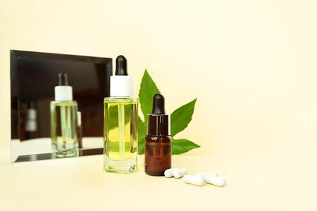 Glass bottles with herbal CBD oil, THC tincture, pills, mirror and hemp leaf on pastel beige background. Flat lay, minimal style. Cosmetics CBD oil. Essential natural oils for face and body.