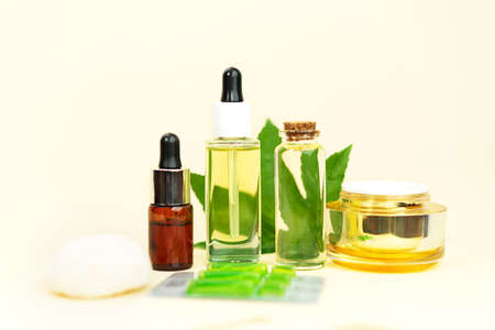 Glass bottles with herbal CBD oil, THC tincture, pills, sponge and hemp leaf on pastel beige background. Flat lay, minimal style. Cosmetics CBD oil. Essential natural oils for face and body. Фото со стока