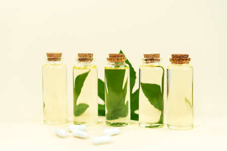 Glass bottles with herbal CBD oil, THC tincture, pills and hemp leaf on pastel beige background. Flat lay, minimal style. Cosmetics CBD oil. Essential natural oils for face and body.