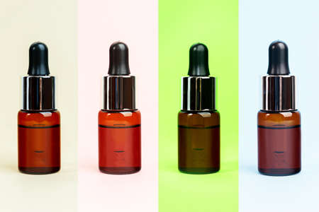 Multi color herbal oil bottles aroma dropper on glass. Essential natural oils for face and body. Organic minimalis layout.