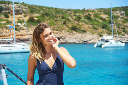 Happy young woman feels happy on the luxury sail boat yacht catamaran in turquoise sea in summer holidays on island. Caucasian female model.