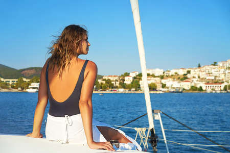 Young happy woman in sunglasses feels fun on the luxury sail boat yacht catamaran in turquoise sea in summer holidays, Greece. Caucasian female model. Selective focus. 免版税图像