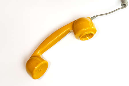 Yellow color handset of a telephone on a white background. Modern retro style. New old technology.