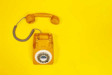 Yellow handset of a telephone on a yellow background. Modern retro style. New old technology.